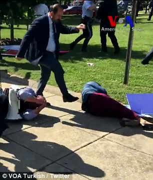 This suited man - believed to be a bodyguard of the Turkish president - was filmed kicking a protester who was on the ground