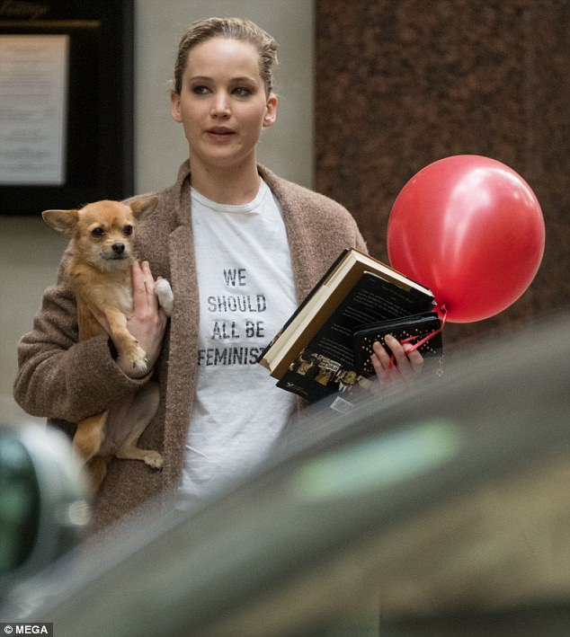 She's got her hands full: The movie star held tight to her pup as she held on to a book and a red balloon while leaving the set