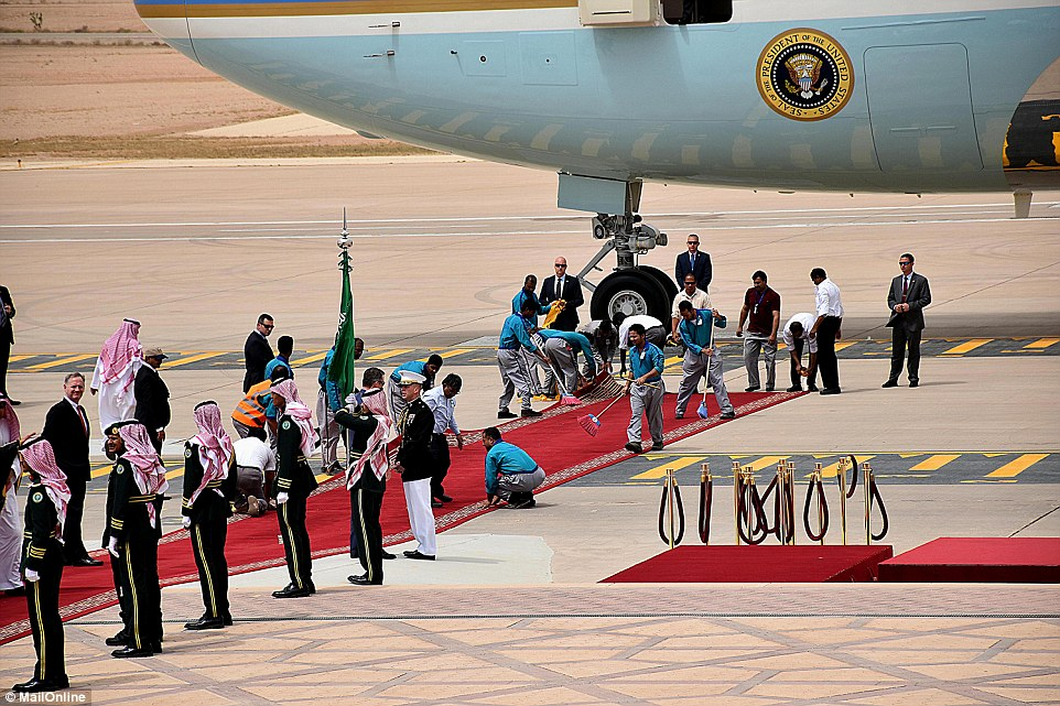The president got the red carpet treatment – literally – and airport workers took off their shoes before manicuring it with brooms in 97-degree heat