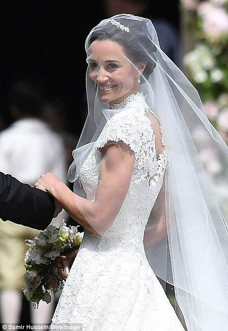 The blushing bride beamed with joy and flashed a smile to the waiting photographers