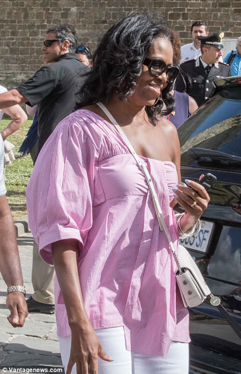 Sunny: Over the weekend, Michelle wore an off-the-shoulder pink top with white ripped jeans and white sandals as she wandered around the stunning Italian hill town of Montalcino