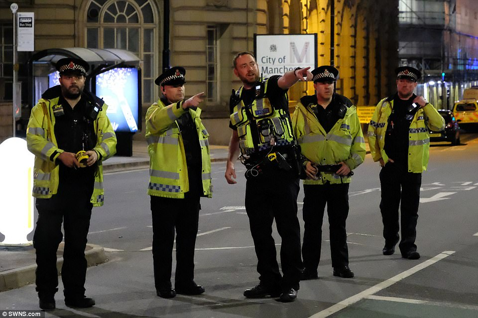 """Police officers stand in a line on a road near Piccadilly Station.Manchester City FC tweeted: """"It's with great sadness we hear of the terrible events at the Arena. Our hearts go out to all affected and to our city's emergency services'"""