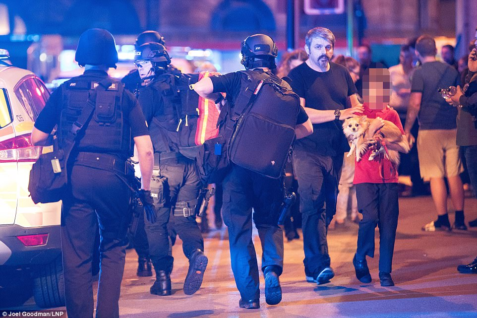 A boy accompanied by an adult carries a dog outside the arena, where crowds of police were gathered. Greater Manchester Police said they will be releasing a contact number for missing people as soon as possible