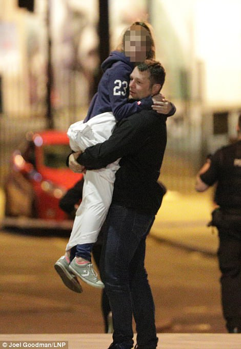 A father carries away his daughter away following the  terror attack at the Ariana Grande concert
