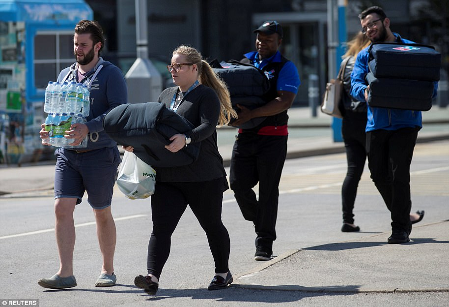 Volunteers as Dominos Pizza delivery drivers bring supplies to the Etihad stadium, where victims' families are being comforted