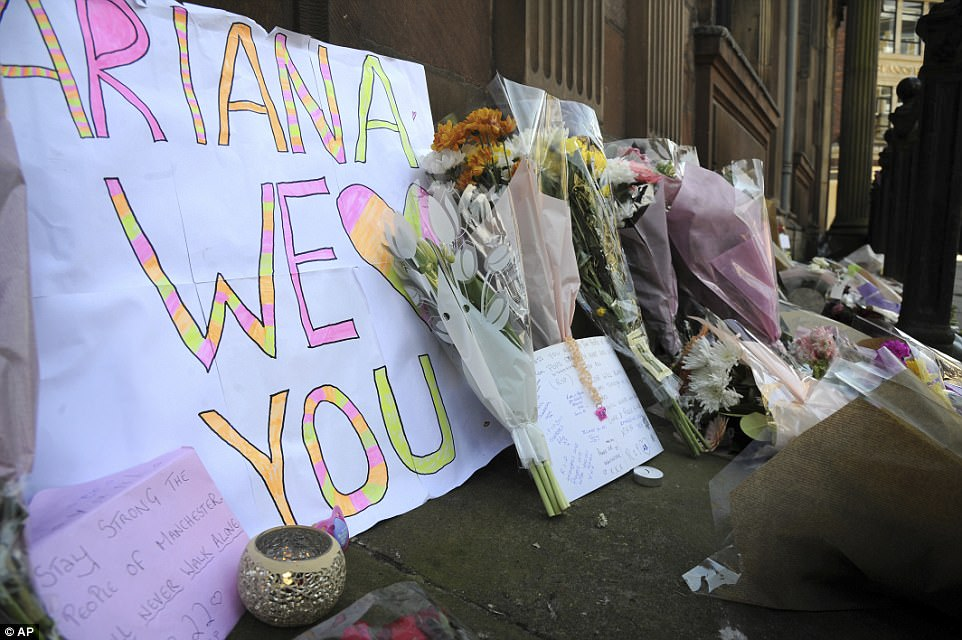 A sign a youngster took to the concert has been incorporated into a sea of floral tributes in the city's St Ann's square