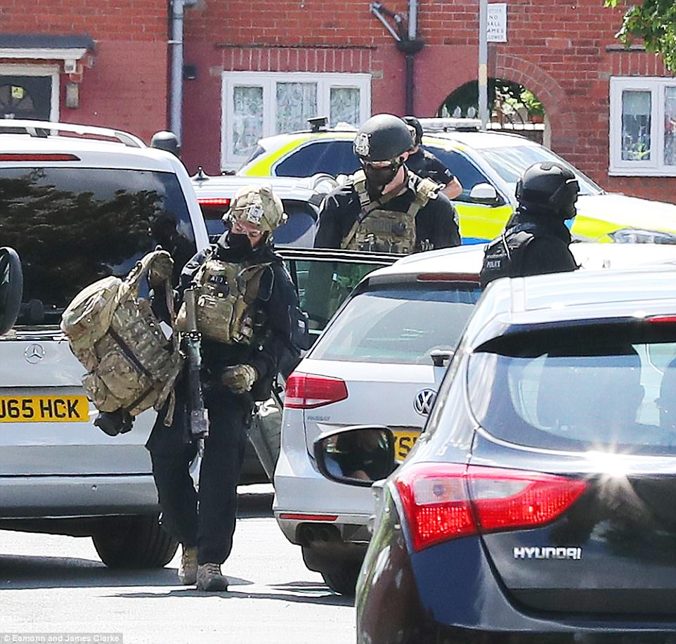 Security service personnel in camouflage were seen entering the property after police burst through the door today