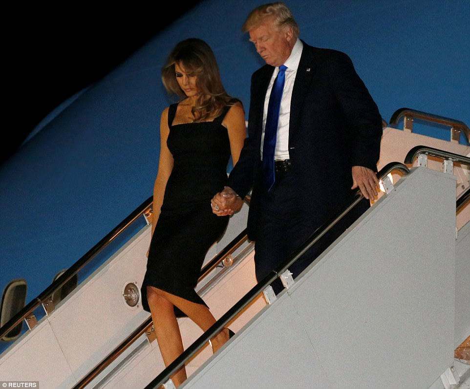 The President and First Lady held hands as they made their way down the steps of Air Force One after arriving at Sigonella Air Force Base in Sicily on Thursday