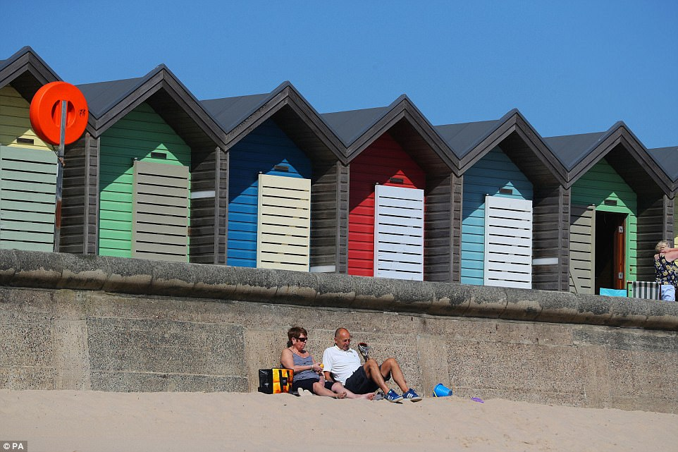 People enjoy the sunshine by the beach huts on Blyth Beach in Northumberland