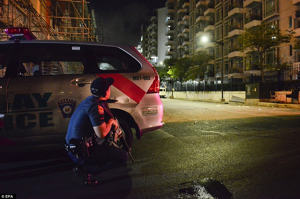At least one masked gunman reportedly stormed the second floor of one of the complex's four hotels and opened fire. An armedFilipino policeman is pictured taking position outside the Resort World Manila