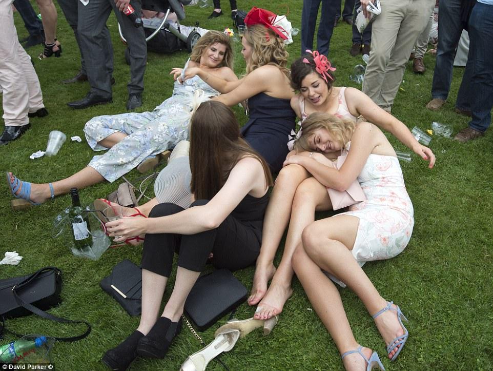 Oque esta acontecendo aqui?  Um grupo de mulheres decidiu fazer uma pausa de assistir as corridas de alguns tomfoolery na grama - e alguns até expulsaram seus sapatos enquanto torciam com seus amigos