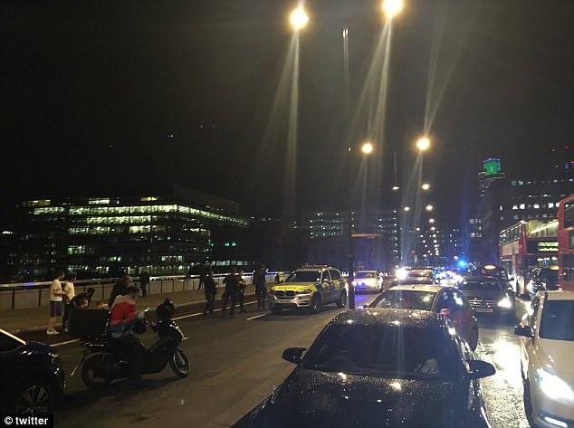 la policía armada y una brigada de explosivos se encuentran en la escena como se ven los barcos en busca del Támesis