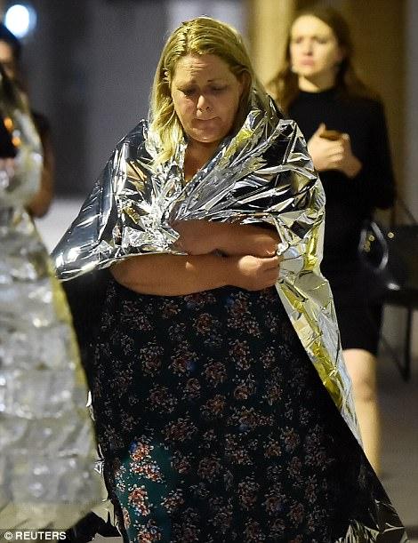 Una mujer emocional se envolvió en una manta de aluminio, mientras la policía la llevó a un lugar seguro