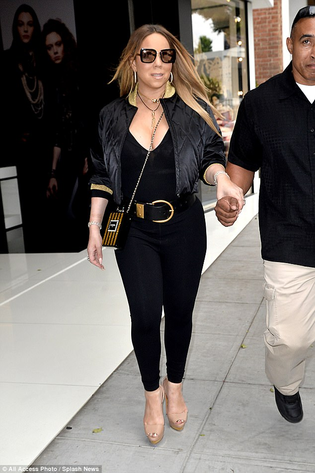 Finishing touches: Wearing her blonde tresses in a sleek centre parting, she accessorised with oversized shades and a funky Chanel bag in the shape of their Number 5 perfume