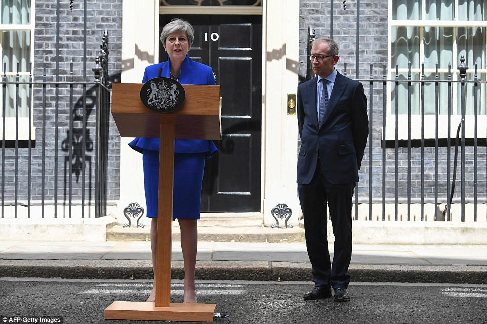 The PM was flanked by husband Philip on the steps of No10 as she delivered her statement after seeing the Queen today
