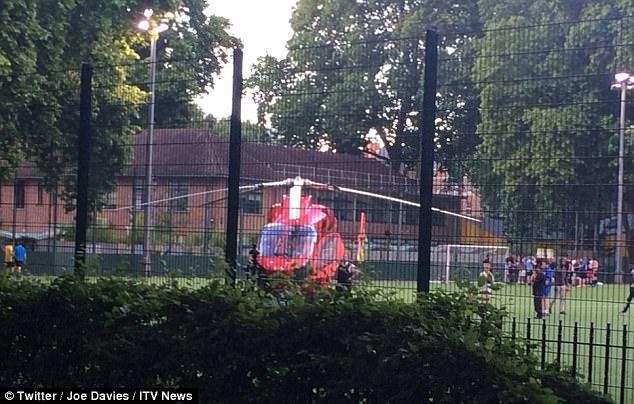 Un helicóptero paramédico aterrizó en un campo de césped artificial cerca, los médicos corrieron a tratar a la víctima