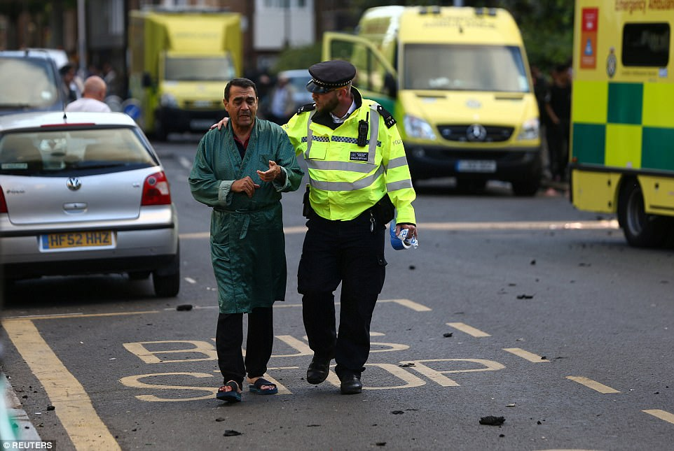 A police officer escorts a resident to safety (pictured) as debris fills the streets around the large building in west London