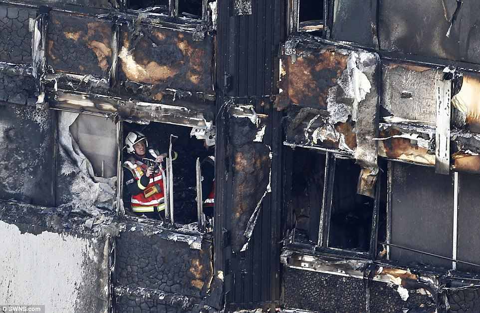 A brave firefighter is pictured inside the burnt remains of the 27-storey building, as efforts are made to investigate what caused the blaze
