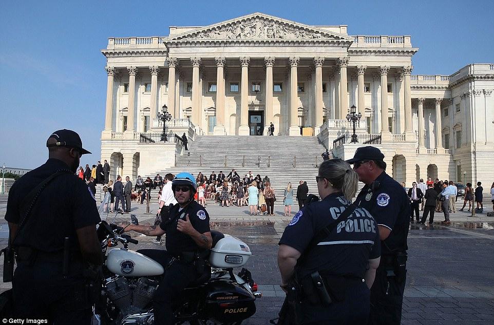 Oficiales fuera del edificio del Capitolio se mantuvieron alerta después de los disparos el miércoles