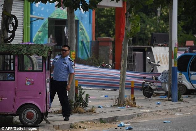 Un policía vigila fuera un jardín de infancia, donde una explosión mató a 8 personas
