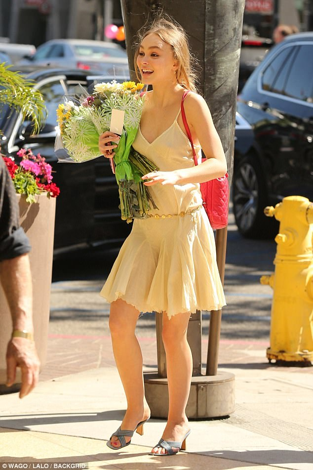 Flower girl: Lily-Rose Depp lived up to her name as she arrived at her former high school bearing bouquets of flowers on Friday