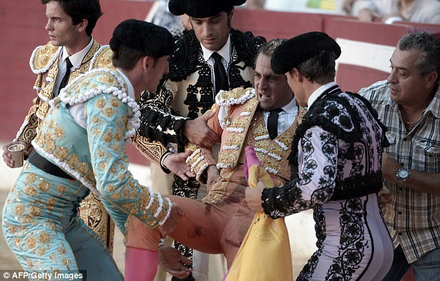 Pictured:Spanish matador Ivan Fandino is carried away after being impaled by a bull
