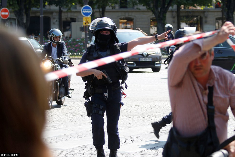 French police secure the area on the Champs Elysees after the car burst into flames in the French capital