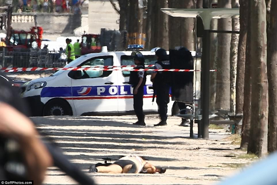 Police standing by as the perpetrator lies face down in the dusty sidewalk after having his clothes ripped from him