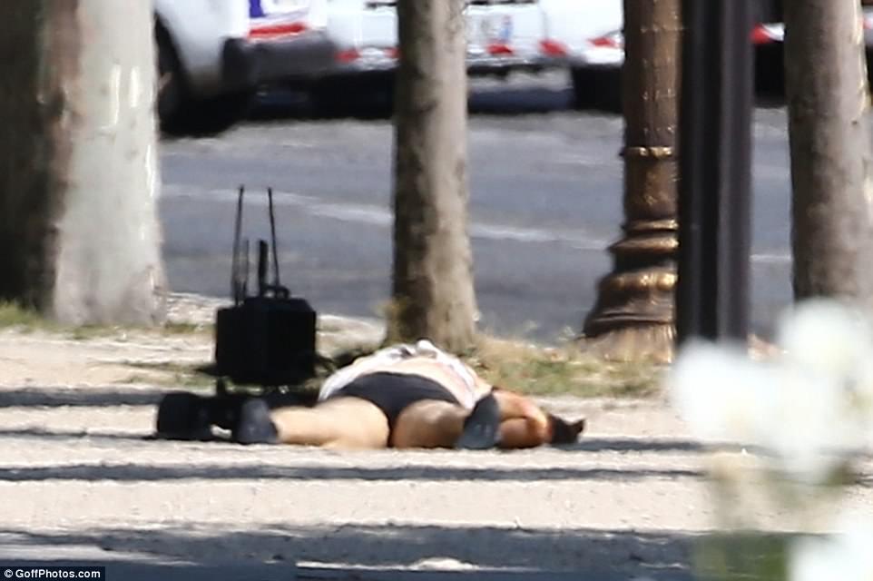 El conductor tendido en el pavimento con un robot de desactivación de bombas cercano después de un oficial de policía arrancó la ropa de él