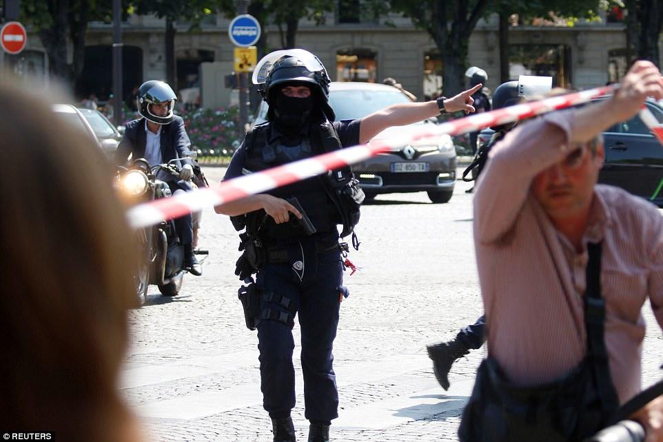 la policía francesa asegurar el área en los Campos Elíseos después de que el coche se incendió en la capital francesa
