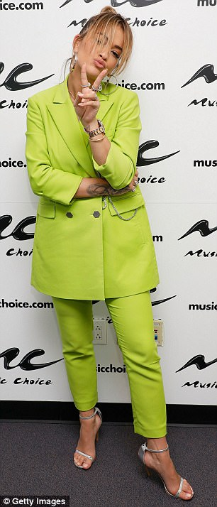 Strike a pose: The songstress later visited Music Choice studios where she pulled faces in her oversized suit