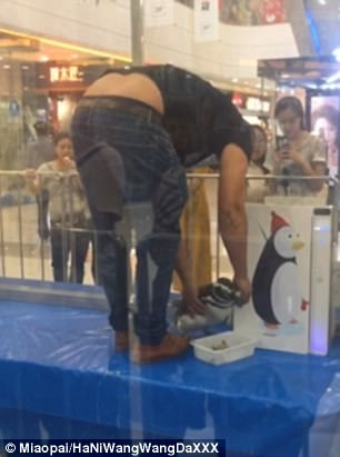 The bird was forced to eat fish as the man appeared to punish it in the shopping mall in China