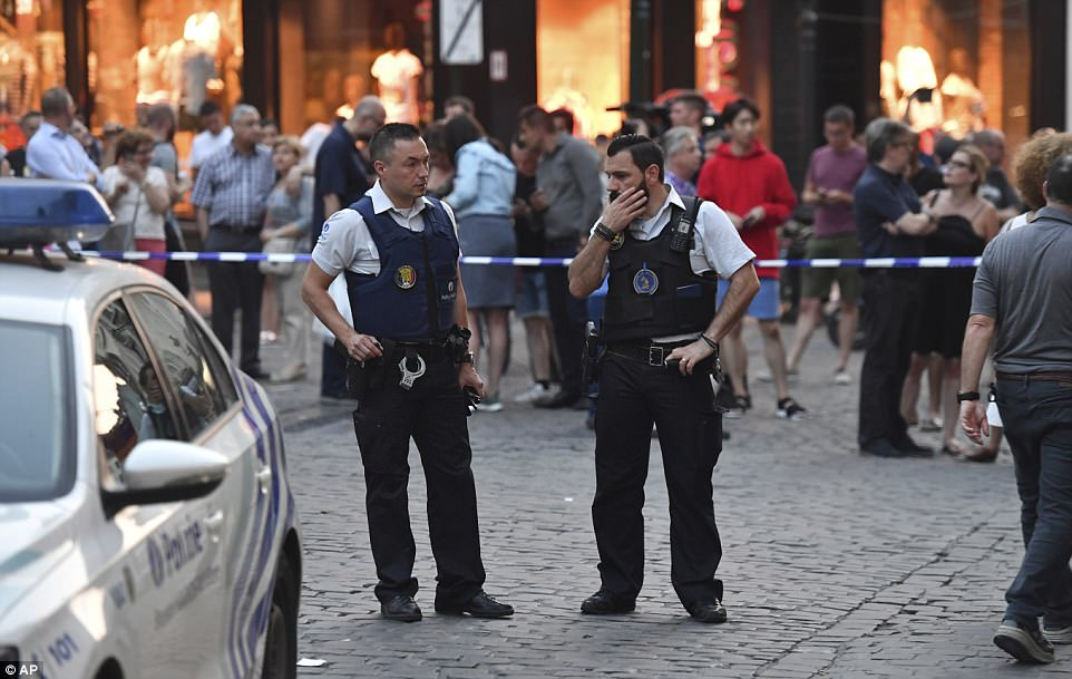 Initial reports suggested the suspect was wearing a rucksack packed with explosives, while witnesses later claimed he tried to blow up a trolley or a suitcase. Pictured, two police men stand guard at the Grand Place square