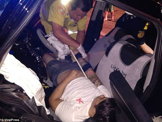 The driver is seen to by a paramedic in Thailand after the horror crash in Chiang Rai