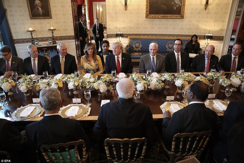The president sat across from Modi and between first lady Melania and Vice President Mike Pence
