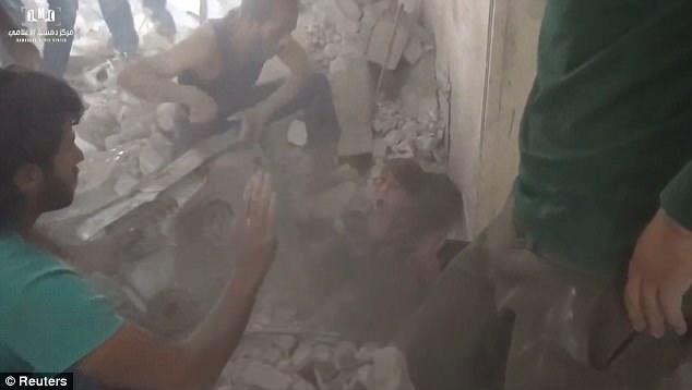 Un equipo de socorristas se apresuran a los dos niños que se encuentran atrapados bajo el enorme montón de escombros en Siria