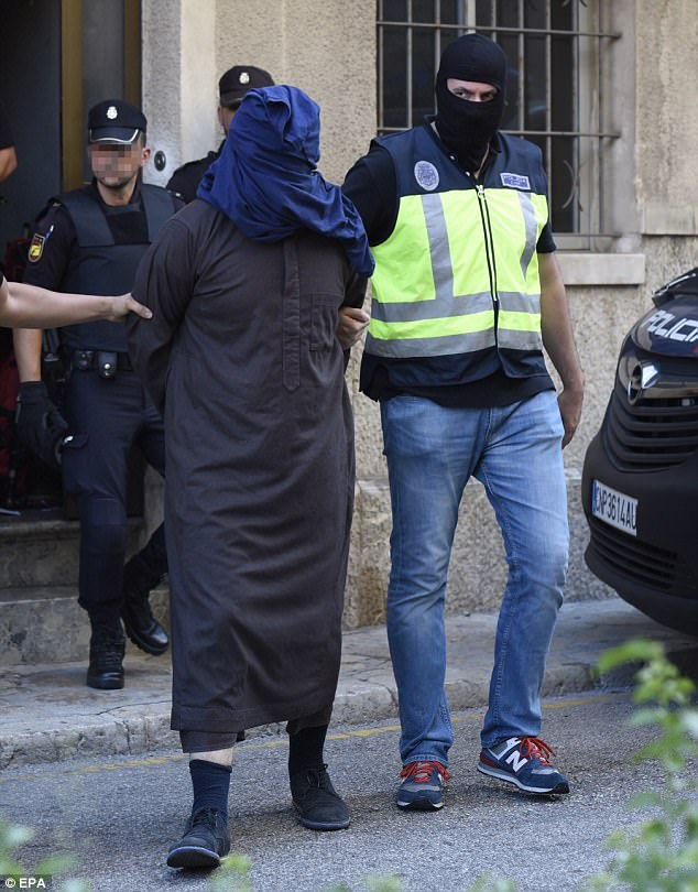 La policía española acompañan a un sospechoso (en la foto), que fue detenido en Mallorca como parte de una operación internacional de terror