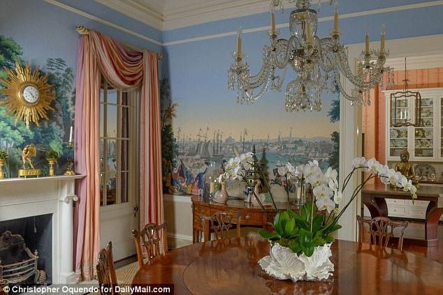 La salle à manger de la maison de Patricia Altschul à Charleston est décorée de peintures murales, d'une horloge et de meubles anciens.