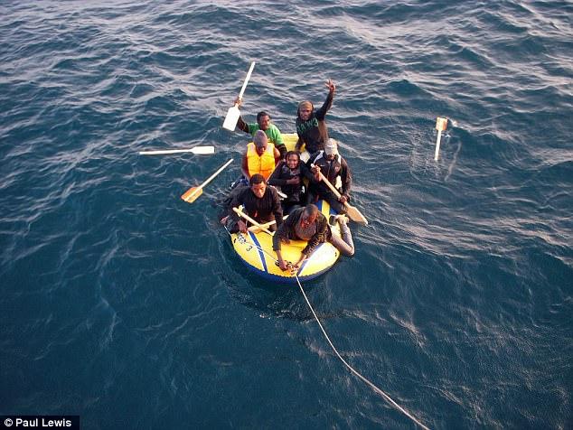 Un grupo de migrantes fueron fotografiados en un bote inflable cerca de la orilla después de ser rescatado