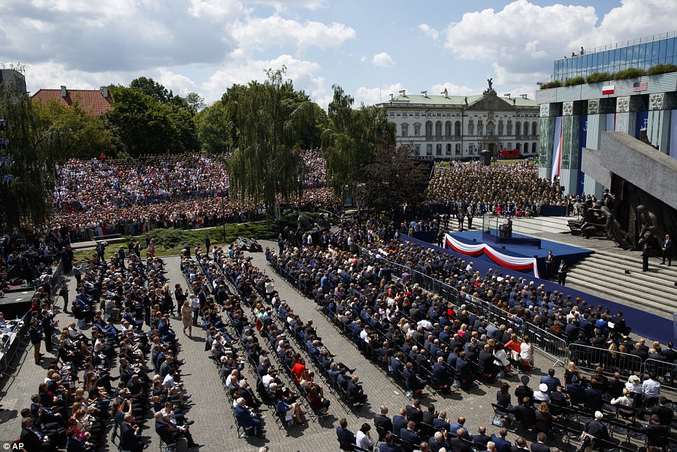 In the center of the square, several rows of seats were set up for guests while others sat in nearby bleachers and behind barriers