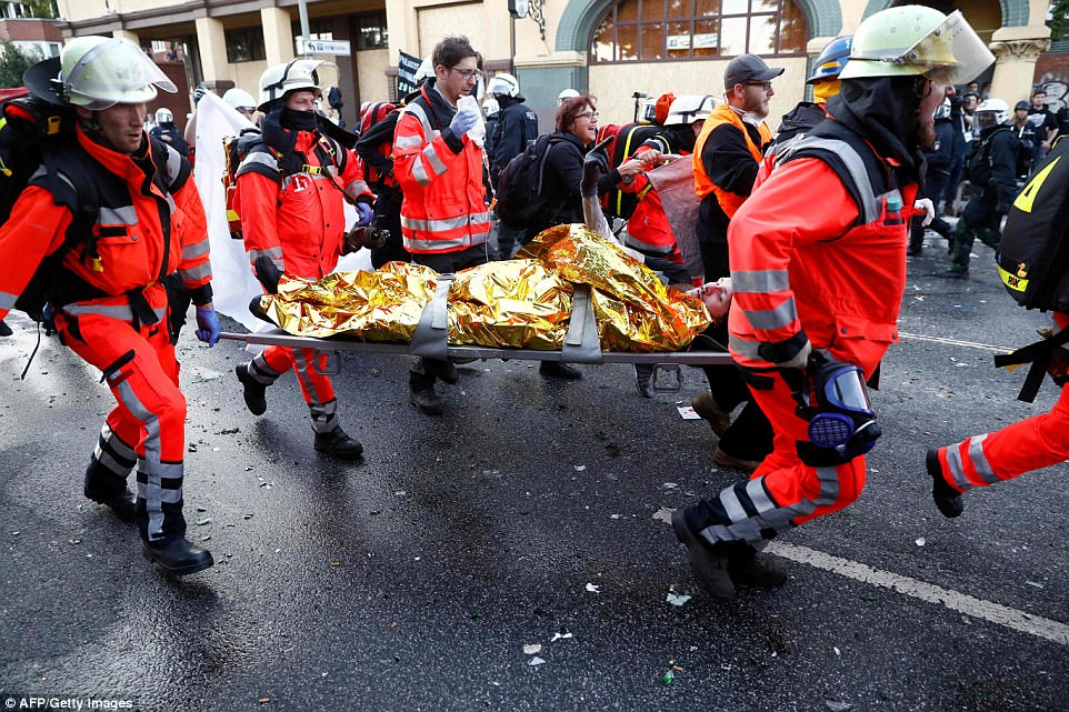 Pictured: An injured protester sticks up his finger as paramedics carry him away from the violence in Hamburg