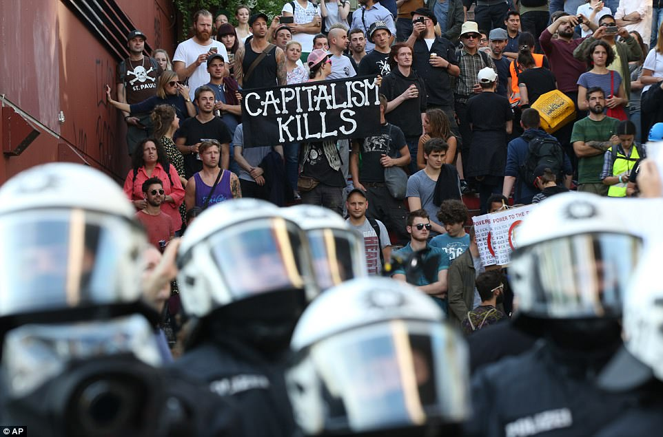 Pictured: Riot police stand next to protesters, one of whom is brandishing a 'capitalism kills' placard