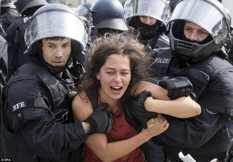 A female protester is detained by several German police officer during demonstrations in Hamburg during the G20 Summit