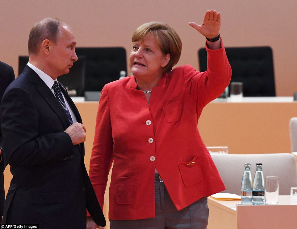 Putin listens to Merkel as she appears to reference someone's height during the first working session of the G20