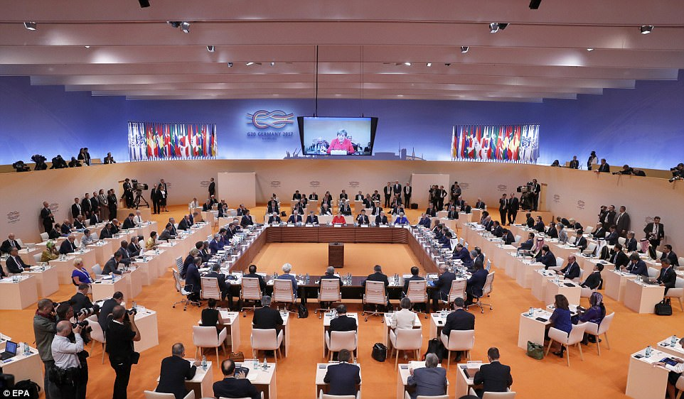 Merkel, sitting in the center of the room in red, spoke to the group of world leaders at the plenary session of the G20 Summit
