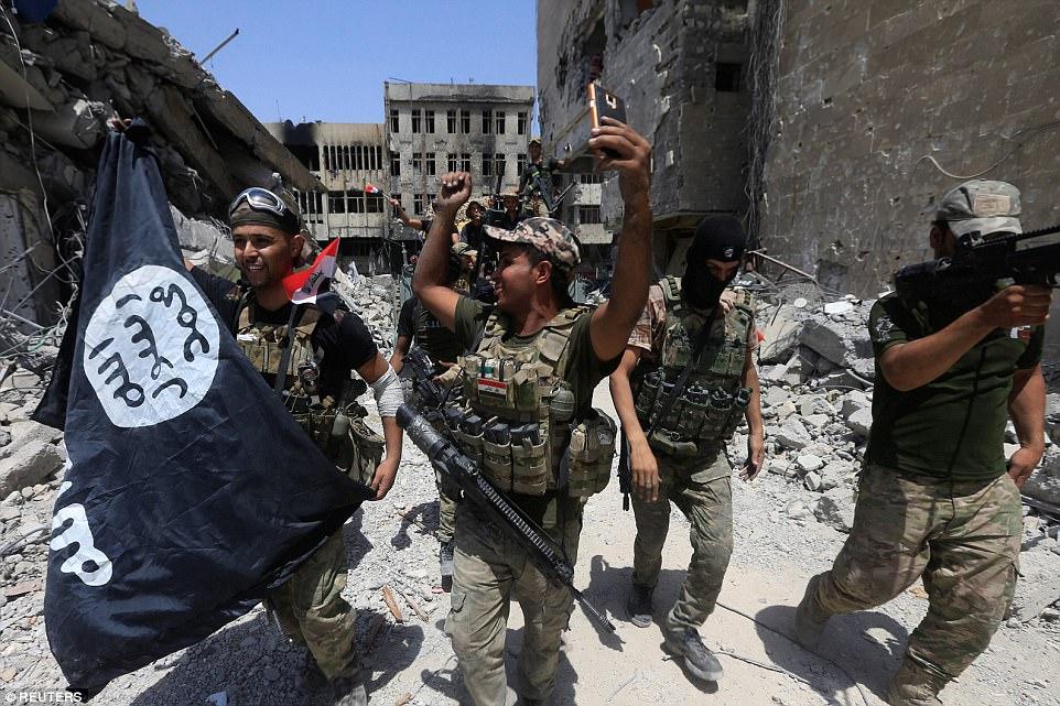 Un oficial del ejército sonriente sostiene una bandera ISIS como la televisión estatal anunció que la victoria será declarada en Mosul 'en horas de esta tarde