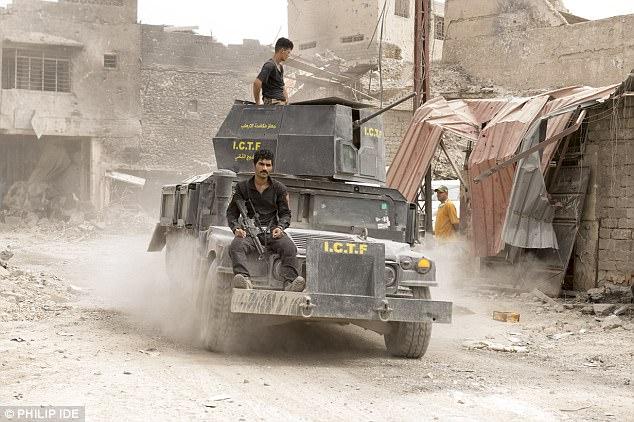 Tropas iraquíes de la coalición montan un tanque a través de la ciudad afectada