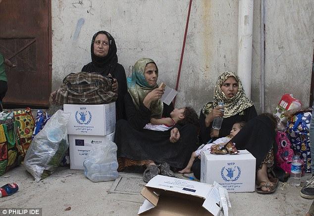 En la foto: mujeres y niños rescatados esperan el transporte mientras la batalla por Mosul entra en sus últimos días