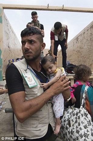 Foto: Un niño es rescatado por un trabajador humanitario en el centro de Mosul mientras las tropas respaldadas por los británicos luchan para liberar la segunda ciudad de Irak