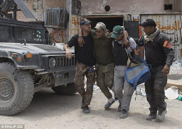 En la foto: Un hombre herido es ayudado a caminar mientras la batalla por Mosul concluye